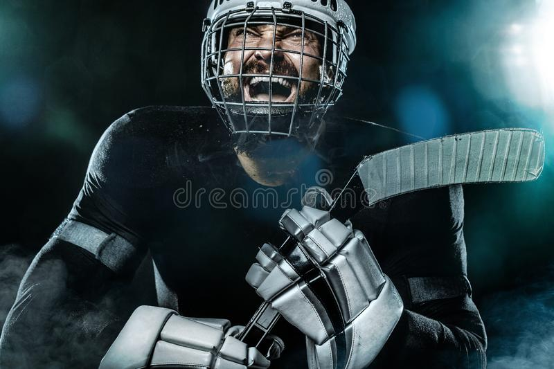 L'uomo felice del giocatore di hockey su ghiaccio nella maschera e nei guanti sullo stadio con il bastone celebra la vittoria Rit immagini stock libere da diritti