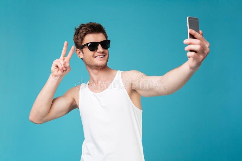 L'uomo felice fa il selfie dal telefono che mostra il gesto di pace immagini stock libere da diritti