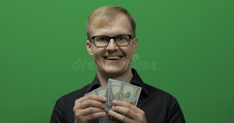 L'uomo felice ha riscosso il biglietto per un affare importante Fatture del dollaro nella mano fotografia stock