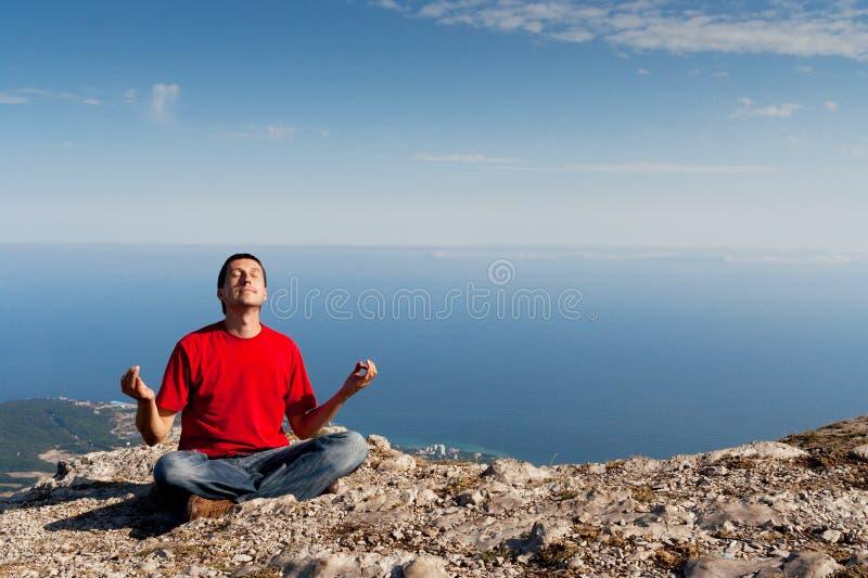 L'uomo felice si siede la posa di yoga sulla montagna fotografia stock libera da diritti