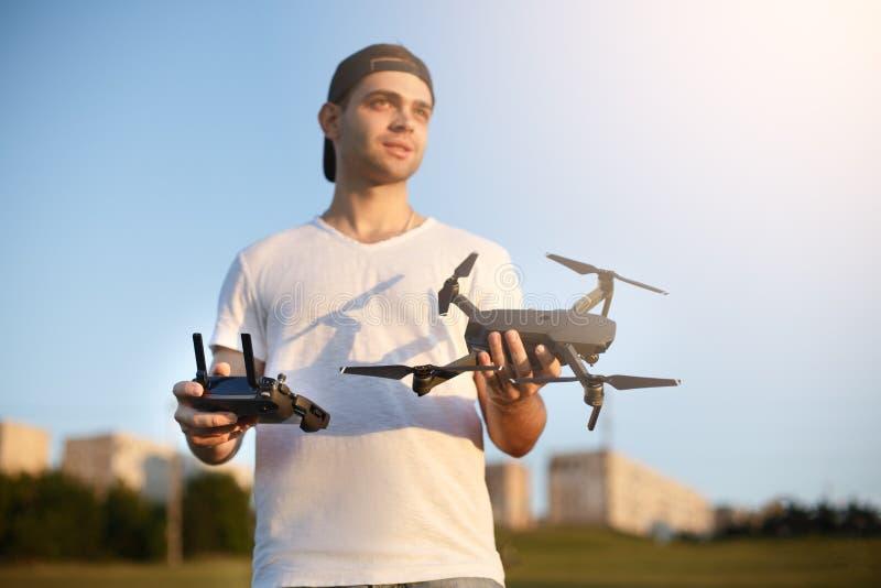 L'uomo felice vi mostra il piccolo fuco compatto ed il regolatore a distanza Il pilota tiene il quadcopter e RC in sue mani fotografia stock libera da diritti