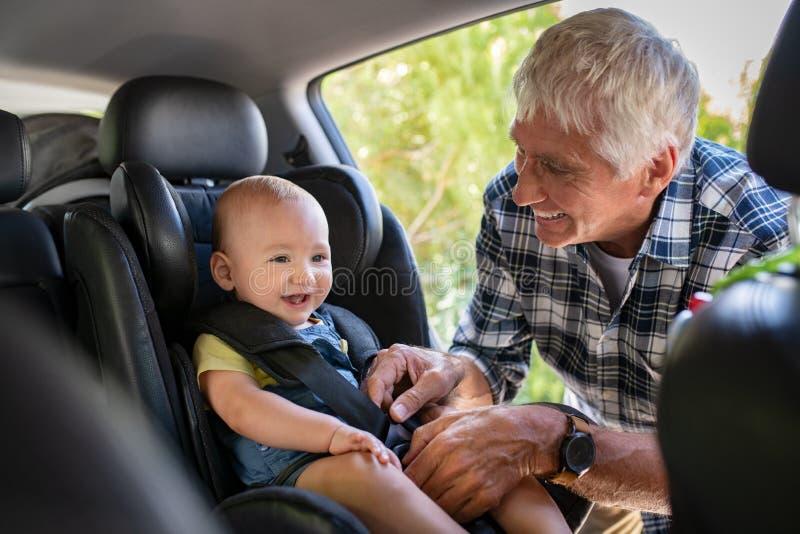 L'uomo fissa la cintura di sicurezza per il bambino sveglio fotografie stock