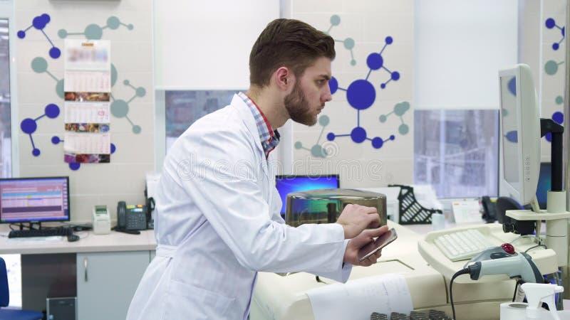 L'uomo fornisce le informazioni dal computer alla compressa al laboratorio immagine stock