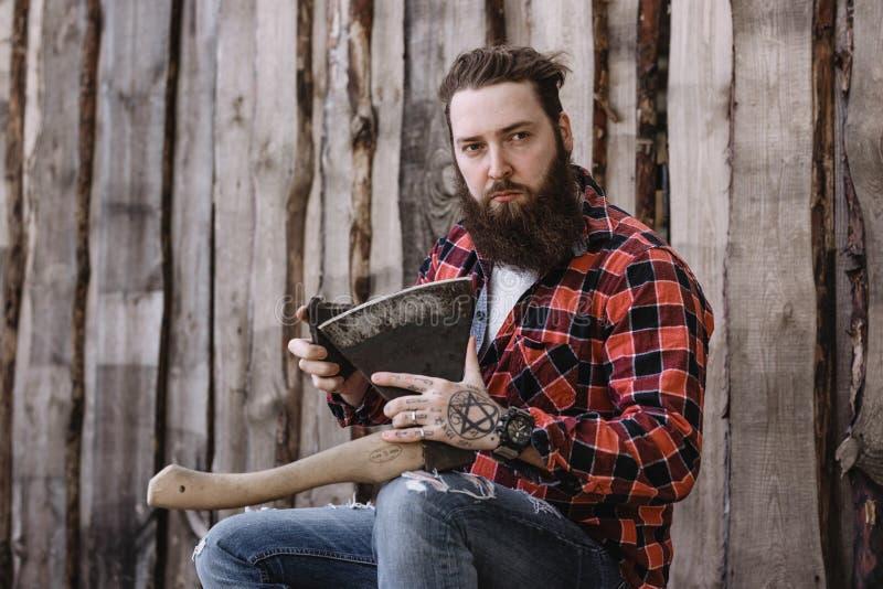 L'uomo forte brutale con una barba vestita in una camicia controllata e nei jeans lacerati ? sedentesi ed affilante l'ascia nelle immagine stock