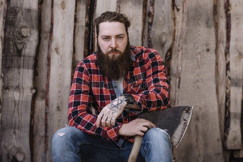 L'uomo forte brutale con una barba vestita in una camicia controllata e nei jeans lacerati sta sedendosi con un'ascia nelle mani  fotografia stock libera da diritti