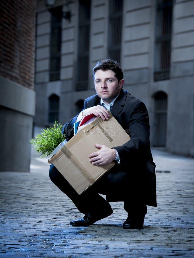 L'uomo frustrato di affari sulla via ha infornato la scatola di cartone di trasporto fotografia stock libera da diritti