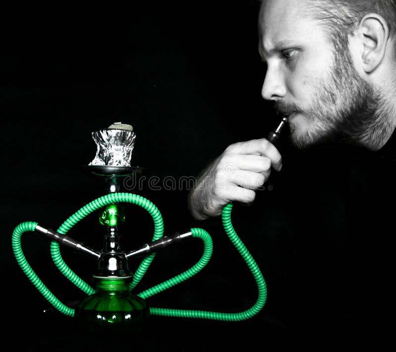 L'uomo fuma un narghilé immagini stock libere da diritti