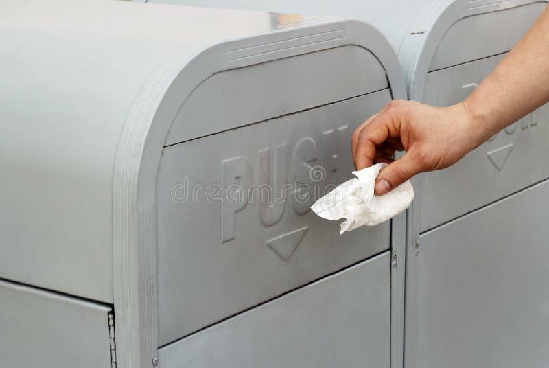 L'uomo getta fuori la carta dei rifiuti nella pattumiera fotografia stock libera da diritti