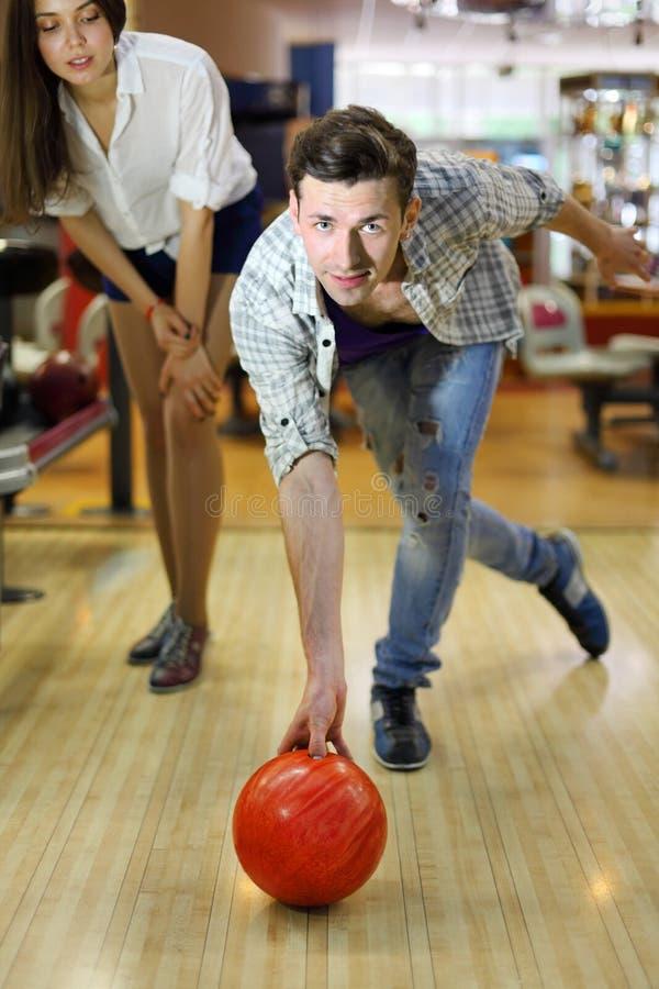 L'uomo getta la sfera nel bowling; la donna esamina l'uomo immagine stock