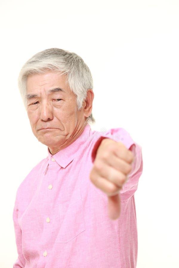 L'uomo giapponese senior con i pollici giù gesture immagini stock libere da diritti