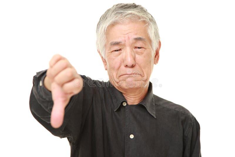 L'uomo giapponese senior con i pollici giù gesture immagine stock libera da diritti