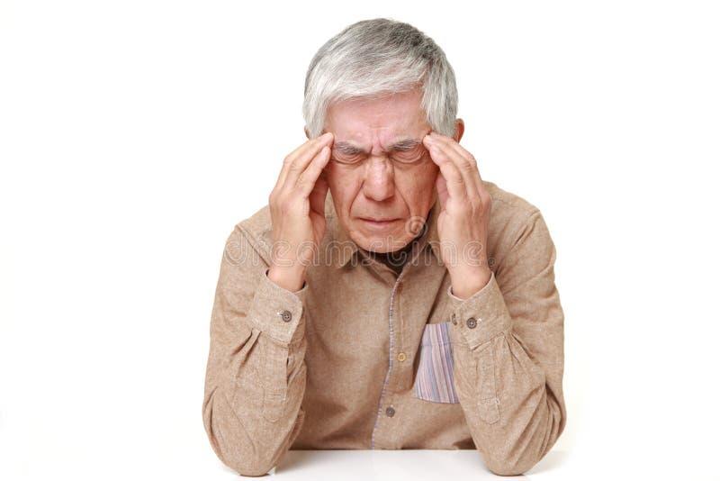L'uomo giapponese senior soffre dall'emicrania immagini stock