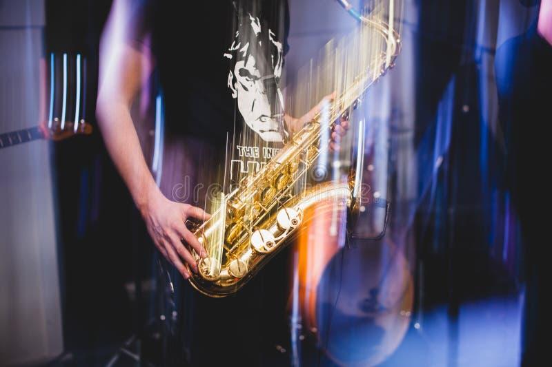 L'uomo gioca la fine del sassofono su Freezelight fotografia stock
