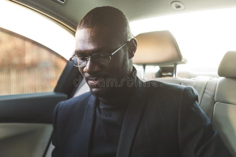 L'uomo giovane di affari nel sedile posteriore in un'automobile costosa va ad una riunione fotografia stock