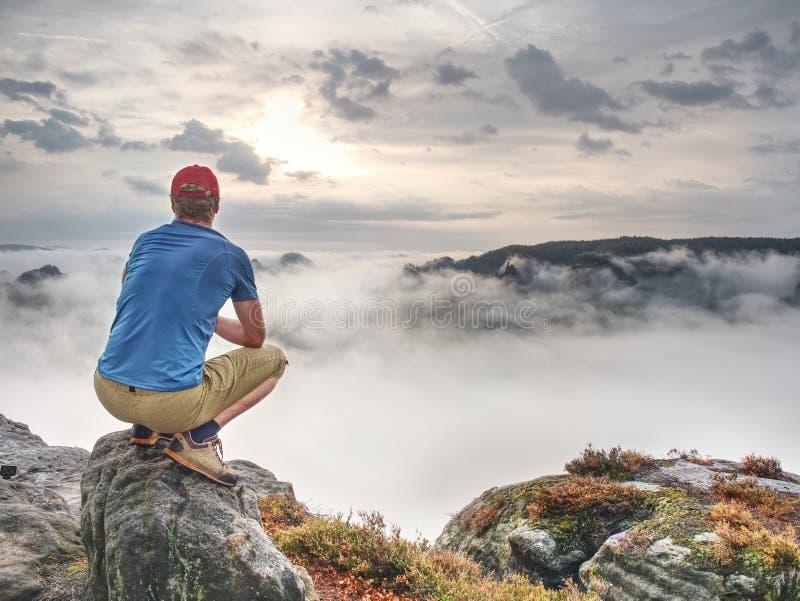 L'uomo gode dell'alba vaga fantastica sopra la montagna rocciosa fotografia stock libera da diritti