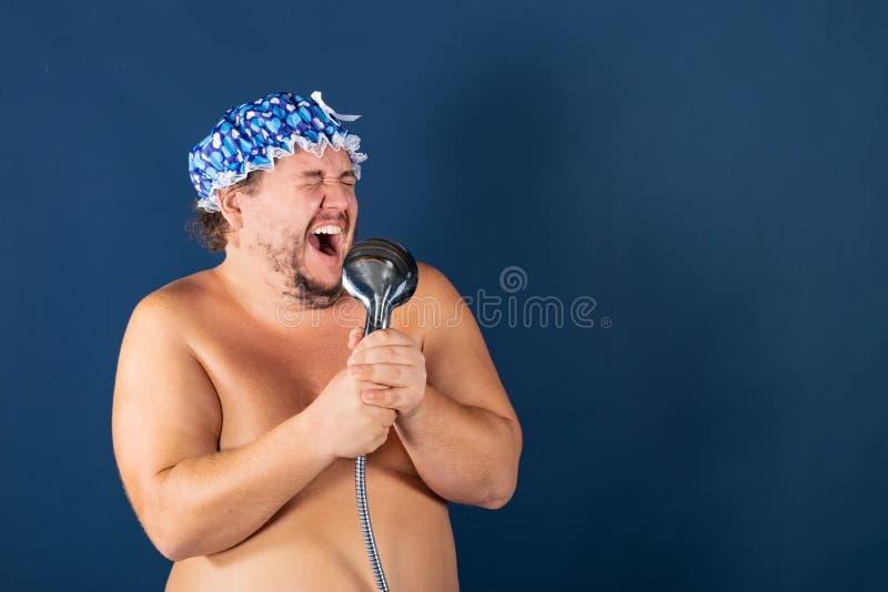 L'uomo grasso divertente in cappuccio blu canta nella doccia fotografia stock libera da diritti