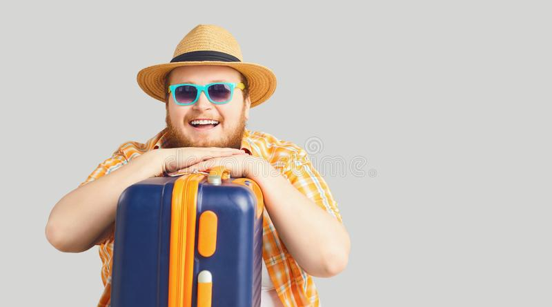 L'uomo grasso divertente in un cappello con una valigia sta sorridendo su un fondo grigio fotografia stock