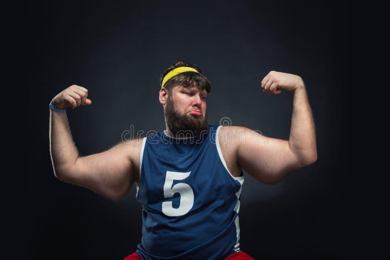 L'uomo grasso mostra il suo muscolo immagine stock