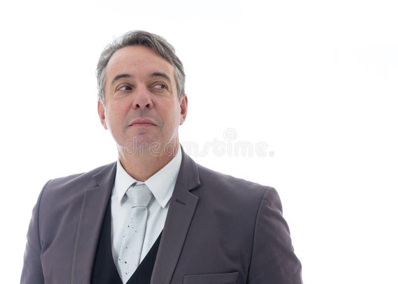 L'uomo guarda lateralmente con un sorriso debole Dirigente in vestito su fondo bianco fotografie stock