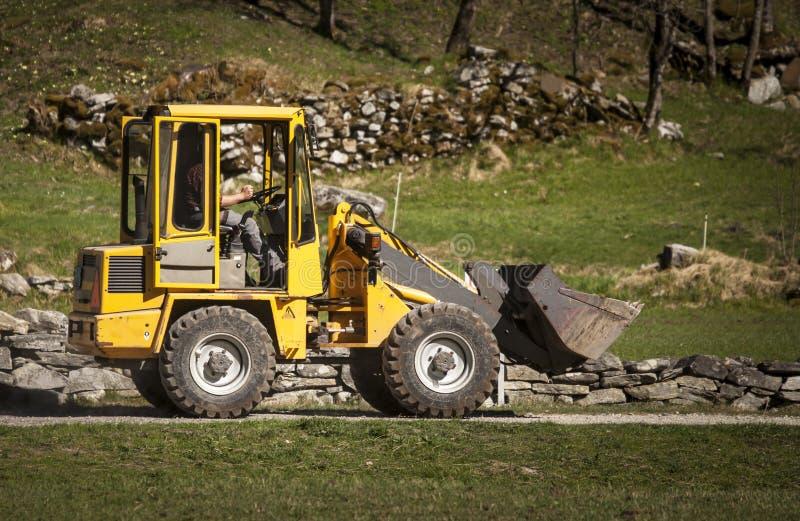 L'uomo guida il caricatore giallo dell'escavatore a cucchiaia rovescia fotografia stock