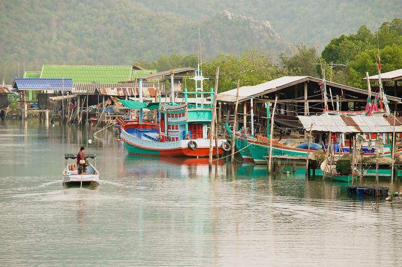 L'uomo guida il motoscafo dal villaggio dei pescatori nel parco di Sam Roi Yot National, Sam Roi Yot, Tailandia fotografia stock