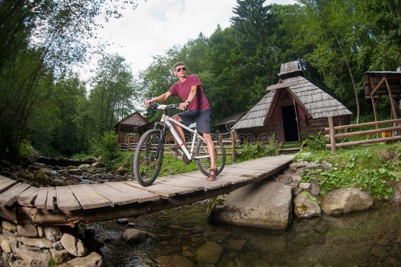 L'uomo guida una bicicletta tramite il ponte di legno sopra un fiume fotografia stock libera da diritti