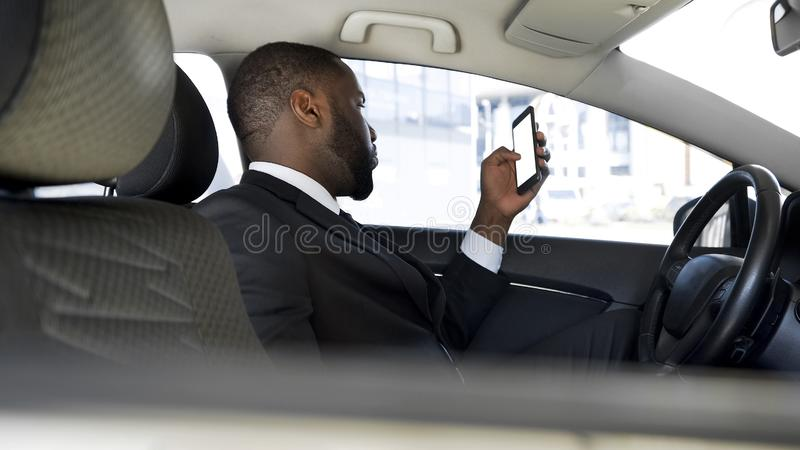 L'uomo ha attaccato in ingorgo stradale, l'applicazione annoiata di notizie di scorrimento sul suo smartphone immagini stock