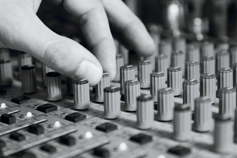L'uomo ha installato il miscelatore per regolare il suono e la registrazione fotografie stock