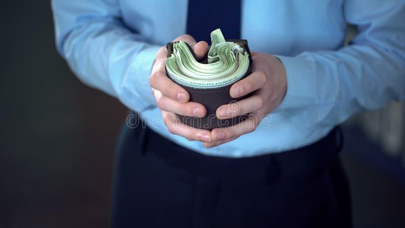 L'uomo ha spinto il grande pacco delle banconote nella borsa, ammortamento di soldi, inflazione immagine stock libera da diritti