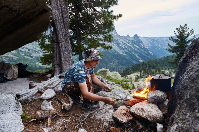 L'uomo ha sviluppato un fuoco di accampamento nel legno in natura Sopravviva a nelle montagne nella foresta, cucinante in una pen fotografia stock