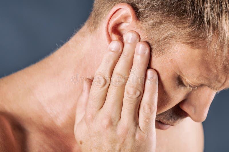 L'uomo ha un orecchio irritato Sofferenza dell'uomo dall'emicrania su fondo blu fotografia stock libera da diritti