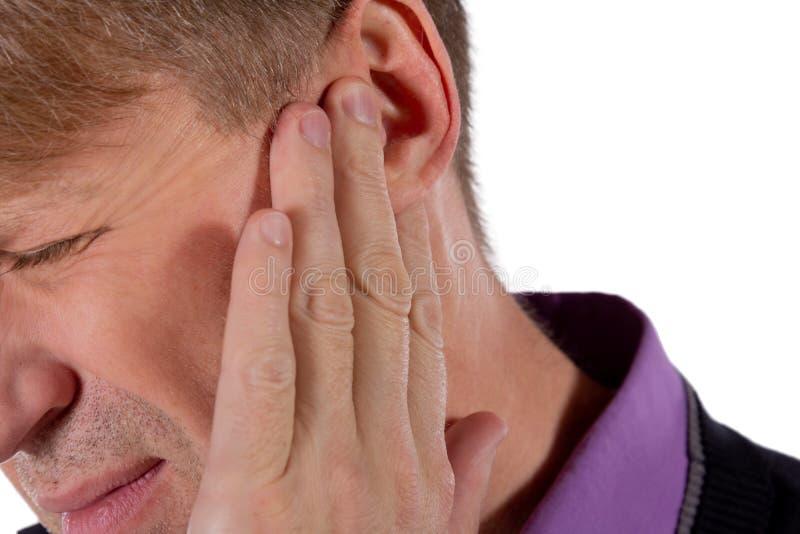L'uomo ha un orecchio irritato Sofferenza dell'uomo dalla mal d'orecchi su fondo bianco fotografie stock libere da diritti