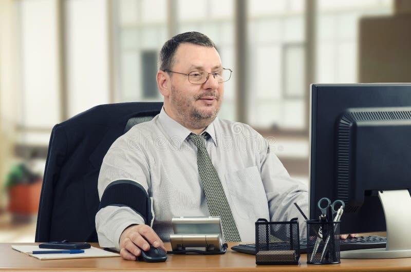 L'uomo impara l'ipertensione in carico nel luogo di lavoro fotografia stock libera da diritti