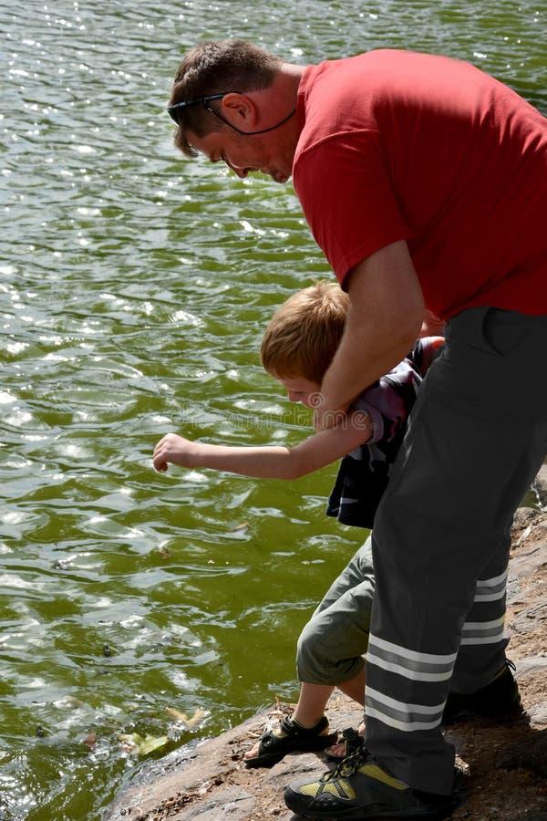 L'uomo impedisce ad un ragazzino di saltare in un fiume immagine stock