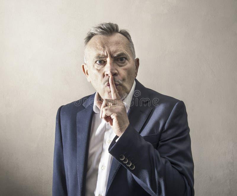 L'uomo impone il silenzio in un modo arrogante immagini stock libere da diritti