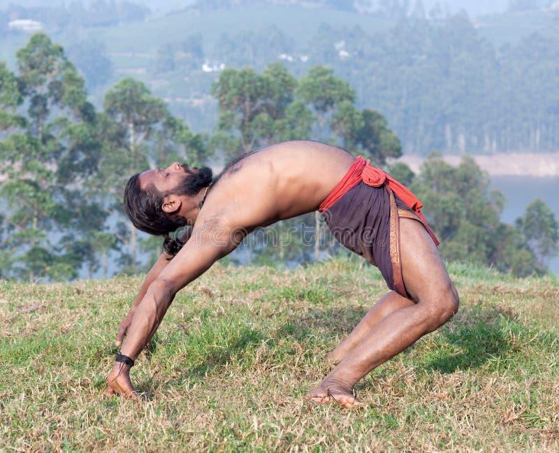 L'uomo indiano che fa l'yoga si esercita su erba verde fotografia stock