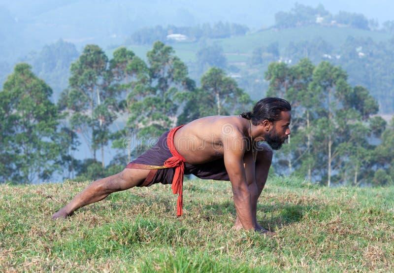 L'uomo indiano che fa l'yoga si esercita su erba verde nel Kerala, verso sud fotografia stock