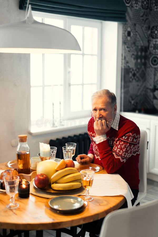 L'uomo infelice anziano sta sedendosi alla tavola fotografie stock libere da diritti