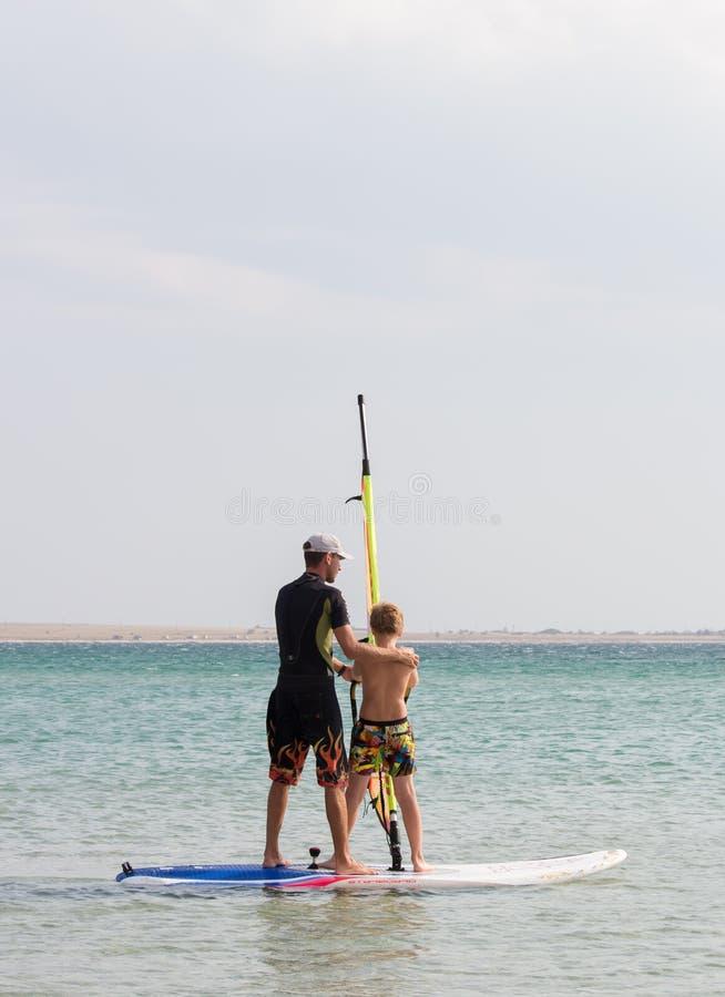 L'uomo insegna ad un ragazzo a guidare il windsurf immagine stock