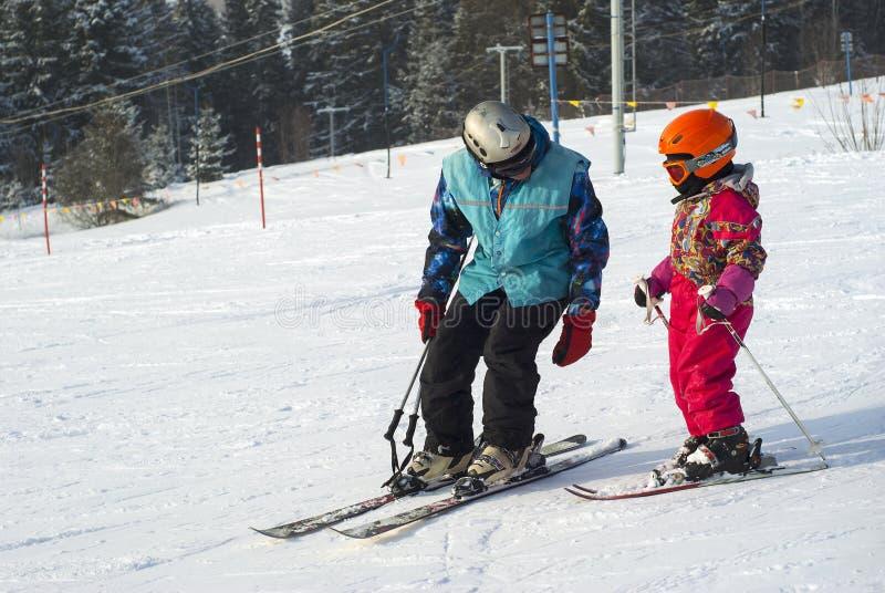 L'uomo insegna ad una corsa con gli sci del bambino su un fianco di una montagna nevoso fotografia stock libera da diritti