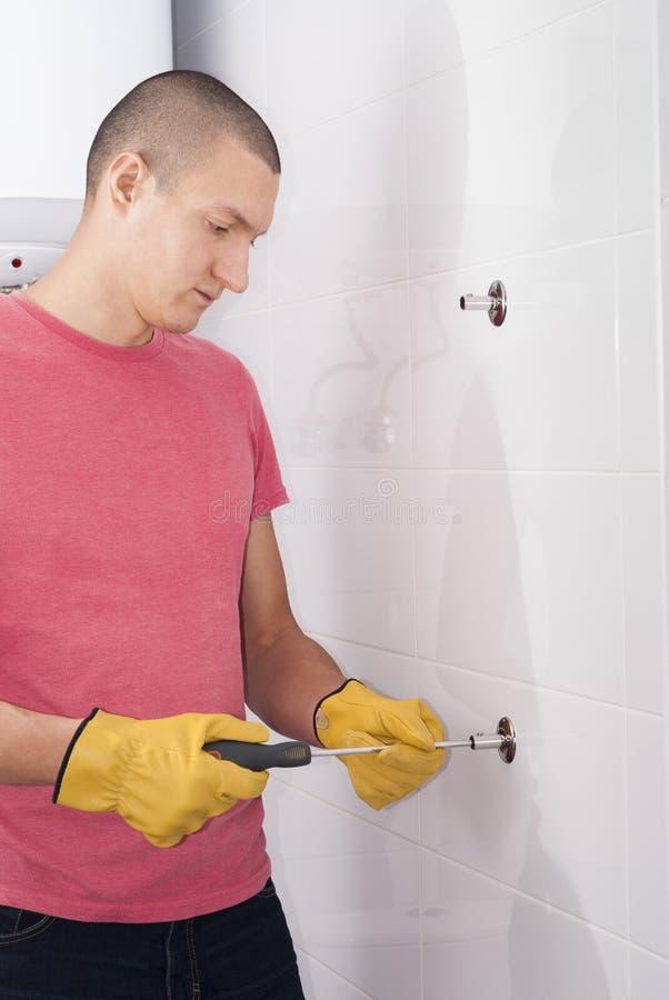 L'uomo installa l'essiccatore dell'asciugamano immagini stock libere da diritti
