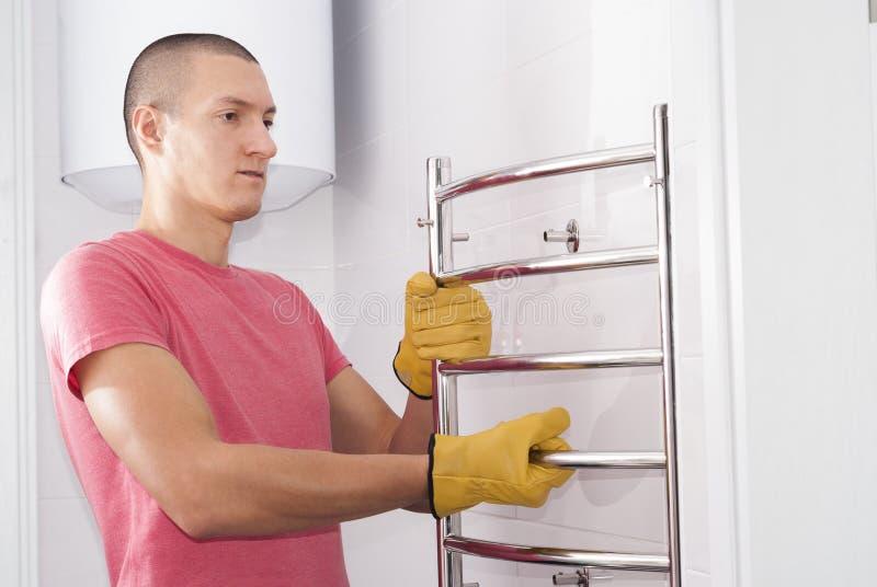L'uomo installa l'essiccatore dell'asciugamano immagini stock