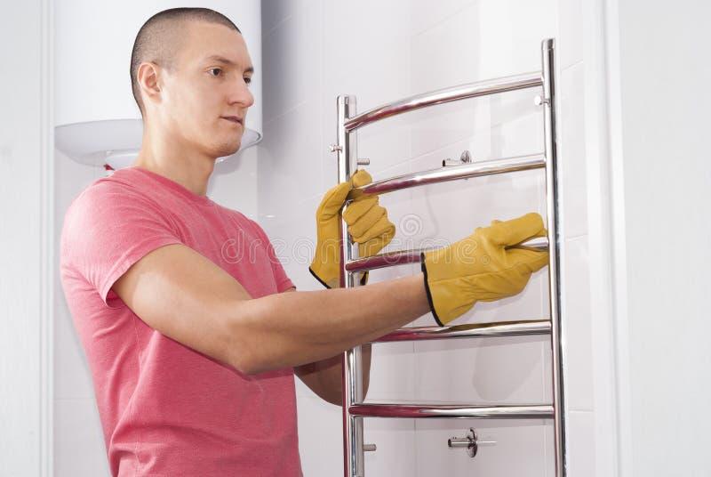 L'uomo installa l'essiccatore dell'asciugamano fotografia stock