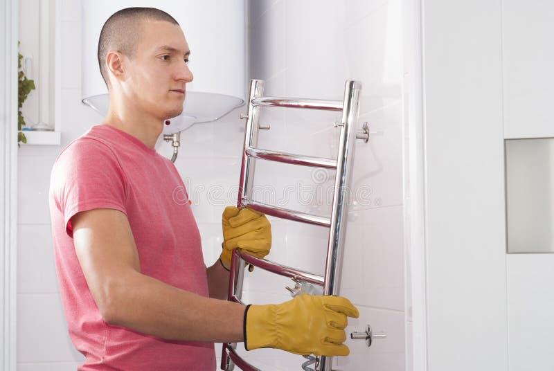 L'uomo installa l'essiccatore dell'asciugamano immagine stock libera da diritti