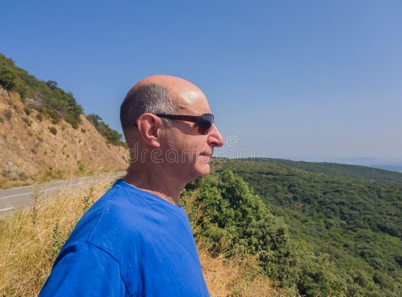 L'uomo invecchiato calvo in occhiali da sole esamina la distanza nella prospettiva sulla valle fotografia stock