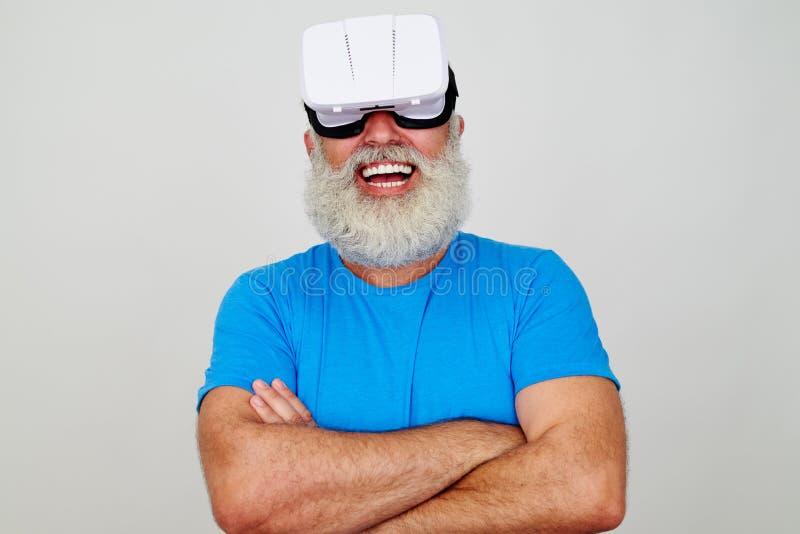 L'uomo invecchiato sorridente con le armi attraversate che indossano la realtà virtuale si dirige fotografia stock libera da diritti