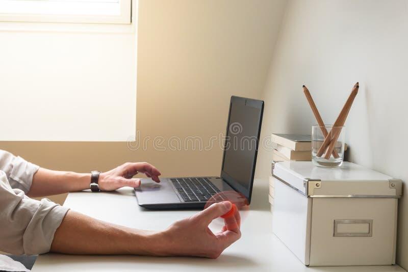L'uomo iperattivo incontra difficoltà che si concentra mentre lavora e giocando con un giocattolo del filatore di irrequietezza fotografia stock