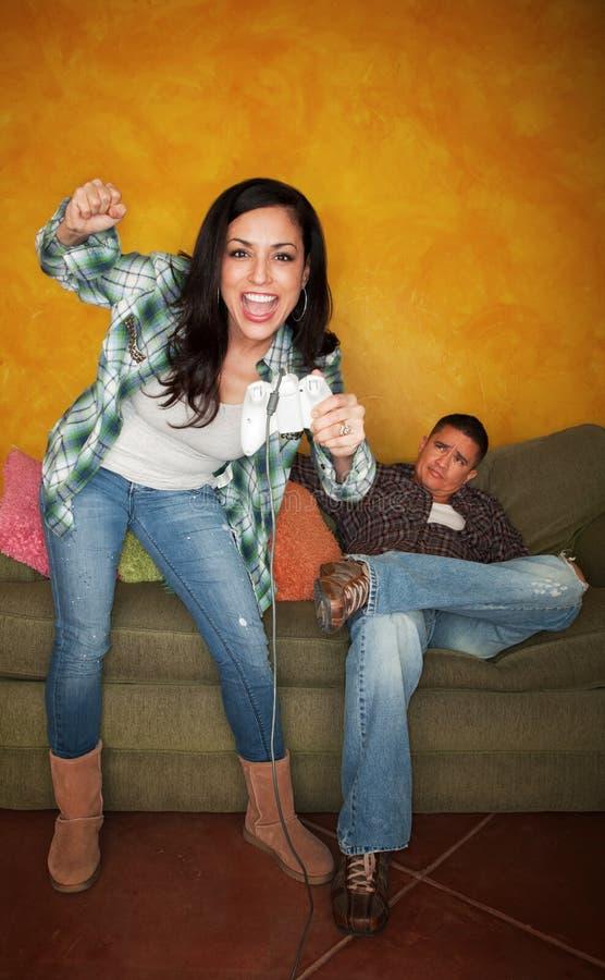 L'uomo ispanico ha alesato mentre la moglie gioca il video gioco fotografia stock libera da diritti