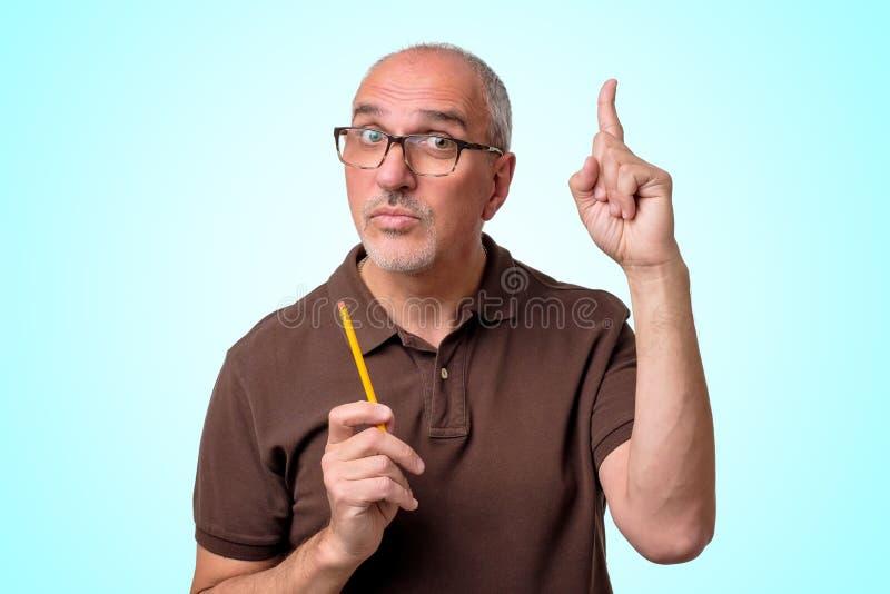 L'uomo ispanico maturo ha una buona idea che sta sul fondo blu L'insegnante sta tenendo la matita fotografia stock libera da diritti