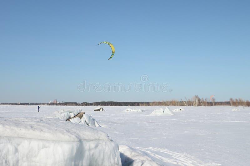 L'uomo kiting sugli sci sul fiume congelato immagine stock